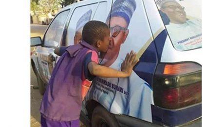 boy kissing Buhari's image on campaign vehicle